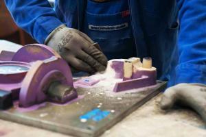Das Anschnittsystem für ein Gussteil aus Gusseisen mit Kugelgraphit wird händisch nachgearbeitet