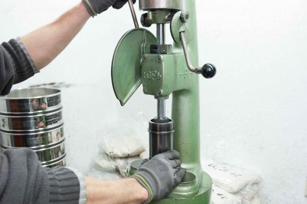 Um die Druckfestigkeit von Formstoff im Sandlabor einer Maschinengiesserei für Grauguss und Sphäroguss zu überprüfen, werden genormte Probeköpergeometrien genutzt.