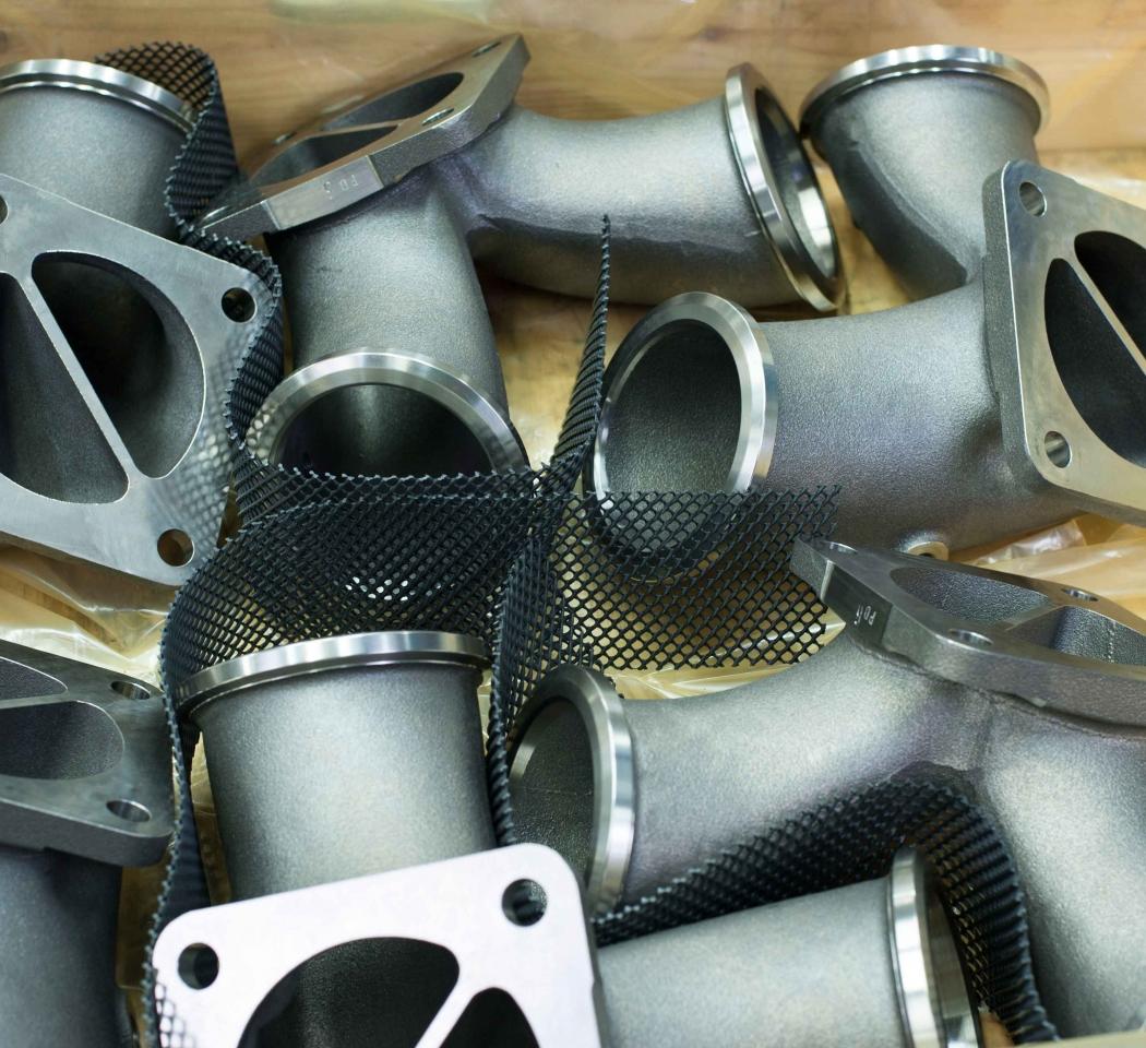 Verpackung von Abgaskrümmern für Großdieselmotoren aus SiMo mit Schutznetz.